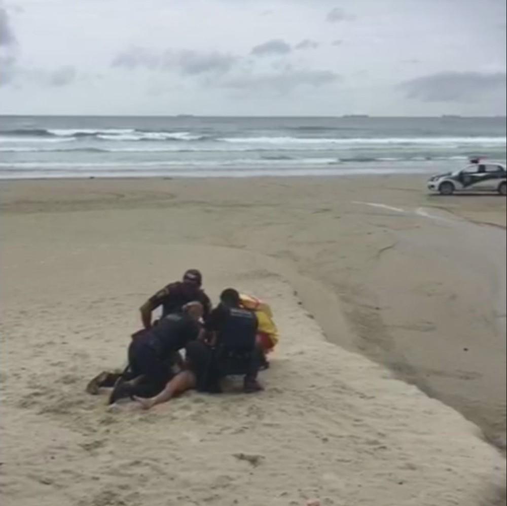 Mulher fura restrição de praia, tenta 'driblar' guardas e acaba imobilizada